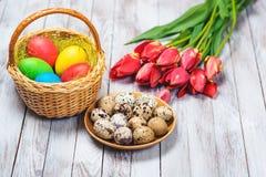 Rote Tulpe und farbige Eier Farbige Ostereier und rote Tulpen auf hölzernem Hintergrund Selektiver Fokus Lizenzfreie Stockbilder
