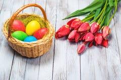 Rote Tulpe und farbige Eier Farbige Ostereier und rote Tulpen auf hölzernem Hintergrund Selektiver Fokus Stockbild