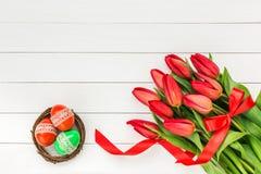 Rote Tulpe und farbige Eier Rote Tulpen und Ostereier auf weißem hölzernem Hintergrund Lizenzfreie Stockfotografie