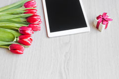 Rote Tulpen, Geschenkbox mit einem roten Bogen und Tablette Stockfoto