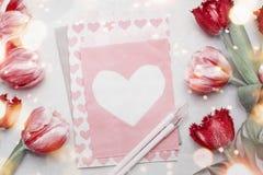 Rote Tulpen um Papier mit Herzen auf Tischplattenhintergrund mit Markierungen, Draufsicht Kreative festliche selbst gemacht Grußk lizenzfreie stockbilder