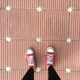 Rote Turnschuh-Schuhe, die auf schmutzige konkrete Draufsicht, Segeltuch-Schuhe gehen auf Beton gehen Stockfotos