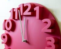 Rote Uhr mit fünf zum Mitternacht Stockbild