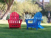 Rote und blaue Adirondack-Stühle auf grünem Rasen lizenzfreie stockfotos