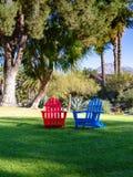 Rote und blaue Adirondack-Stühle im Schatten der Kiefer lizenzfreie stockfotografie