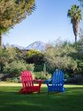 Rote und blaue Adirondack-Stühle am Morgen lizenzfreie stockbilder