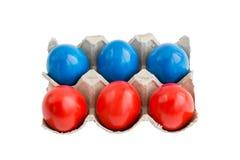 Rote und blaue Eier im Kasten lokalisiert über Weiß Lizenzfreies Stockfoto