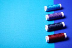 Rote und blaue Nähgarne auf doppel-farbigem Hintergrund lizenzfreie stockfotografie