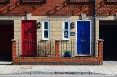 Rote und blaue Nachbartüren im Ziegelstein ummauerten Mannschaftshaus Stockbild