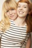 Rote und blonde behaarte Freundinnen lachen und umarmen Lizenzfreie Stockbilder