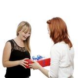 Rote und blonde behaarte Mädchen geben Geschenkkasten Stockfotografie