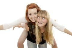 Rote und blonde behaarte Mädchen haben Spaß piggypack Lizenzfreie Stockfotografie