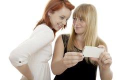 Rote und blonde behaarte Mädchen zeigen etwas am Telefon Stockbilder