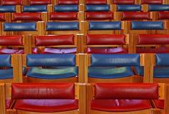 Rote und einfarbige Kirchenbänke Stockfoto