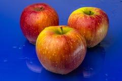 Rote und gelbe Äpfel auf einem blauen Hintergrund Stockbild