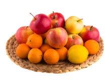 Rote und gelbe Äpfel, Tangerinen und Zitronen auf einer Strohmatte Lizenzfreies Stockfoto