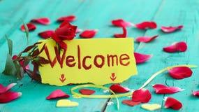 Rote und gelbe Anmerkungskarte mit den roten rosafarbenen Blumenblättern und den Herzen auf blauem hölzernem Hintergrund der anti Lizenzfreie Stockbilder