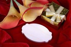 Rote und gelbe Callalilie blüht goldene Geschenkbox mit gelbem Band auf roter Gewebehintergrundkarte für Text Kopieren Sie Platz Stockfoto