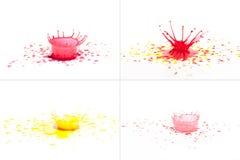 Rote und gelbe Farbe, die auf Weiß spritzt. Lizenzfreies Stockbild