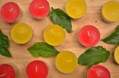 Rote und gelbe Kerzen mit grünen Blättern Lizenzfreie Stockfotos