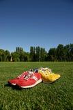 Rote und gelbe laufende Schuhe auf einem Sportfeld Stockfotografie