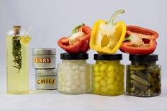 Rote und gelbe Pfeffer, Konserven und Olivenöl im Speiseschrank lizenzfreie stockbilder