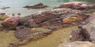 Rote und gelbe Sandsteine auf Strand lizenzfreie stockfotos