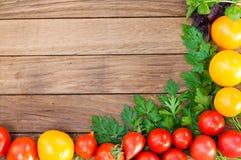 Rote und gelbe Tomaten, Petersilie, Basilikum auf einem Holztisch stockbild