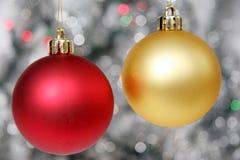 Rote und gelbe Weihnachtskugel gegen Hintergrund von Weihnachtsli Stockfotografie