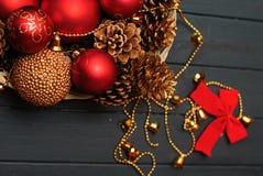Rote und goldene Weihnachtsdekorationen auf hölzernem Hintergrund Stockfoto