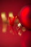 Rote und goldene Weihnachtsverzierungen auf rotem Hintergrund mit Kopienraum Stockbild