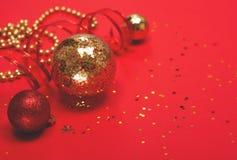 Rote und Goldweihnachtsverzierungen auf rotem Hintergrund stockfotos