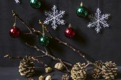 Rote und grüne Bälle, Schneeflocken mit den trockenen Zweigen, Kiefernkegel, Nüsse Stockfoto