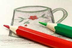 Rote und grüne Bleistifte auf dem Hintergrund einer Kind-` s Zeichnung Lizenzfreie Stockfotos