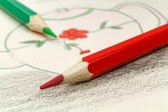 Rote und grüne Bleistifte auf dem Hintergrund einer Kind-` s Zeichnung Stockbild