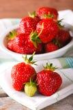 Rote und grüne Erdbeeren auf Tuch vor Schüssel Stockbilder
