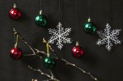Rote und grüne helle Bälle mit Schneeflocken Stockfotografie