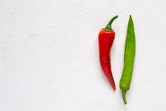 Rote und grüne Peperoni auf einem weißen Hintergrund Stockfotografie