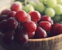 Rote und grüne Trauben in der hölzernen Schüssel Stockfotos