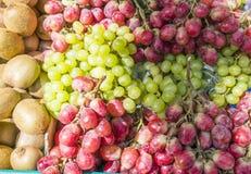 Rote und grüne Trauben und Kiwifruit in einem Markt stockfoto
