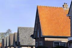 Rote und graue mit Ziegeln gedeckte Dächer in Folge stockbilder
