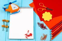 Rote und orange Bleistifte, Filzstifte, Briefpapier, Büroklammern, Briefpapiernägel, Filz und Scheren auf blauem hölzernem Hinter Stockbild