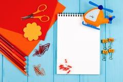 Rote und orange Bleistifte, Filzstifte, Briefpapier, Büroklammern, Briefpapiernägel, Filz und Scheren auf blauem hölzernem Hinter Lizenzfreie Stockbilder