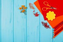 Rote und orange Bleistifte, Filzstifte, Briefpapier, Büroklammern, Briefpapiernägel, Filz und Scheren auf blauem hölzernem Hinter Lizenzfreies Stockbild