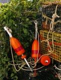 Rote und orange Bojen mit Hummertopf und -seilen Lizenzfreie Stockfotos
