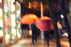 Rote und orange Regenschirme unter Regen Stockbilder