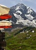 Rote und Sahneregenschirme auf Berg Lizenzfreie Stockfotos