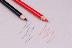 Rote und schwarze Bleistift- und Zickzacklinie auf beige Pastellpapiergrobkornschmutzbeschaffenheit Stockfotos