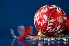 Rote und silberne Weihnachtsverzierungen auf dunkelblauem Hintergrund Lizenzfreies Stockfoto