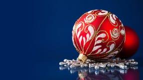 Rote und silberne Weihnachtsverzierungen auf dunkelblauem Weihnachtshintergrund Stockbild